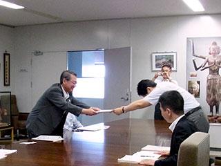 懇談の冒頭、保護者啓発に関する子どもネット研の活動報告書を米田教育長に提出する坂元座長